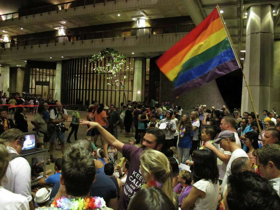 Proponents of gay marriage rally outside House chambers at the Hawaii Capitol in Honolulu on Friday, Nov. 8, 2013. The House debate played out into the night amid noisy crowds outside the chamber and maneuvering inside from lawmakers for and against the bill. (AP Photo/Oskar Garcia) Photo: Oskar Garcia, STF / AP