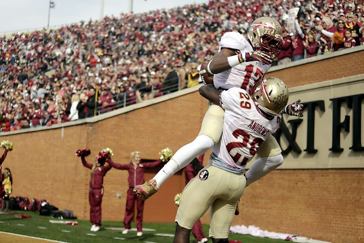 Florida State defensive back Jalen Ramsey, top, jumps into the arms of teammate Nate Andrews after Andrews ran back an interception for a touchdown against Wake Forest in the first half of an NCAA college football game in Winston-Salem, N.C., Saturday, Nov. 9, 2013. (AP Photo/Nell Redmond)
