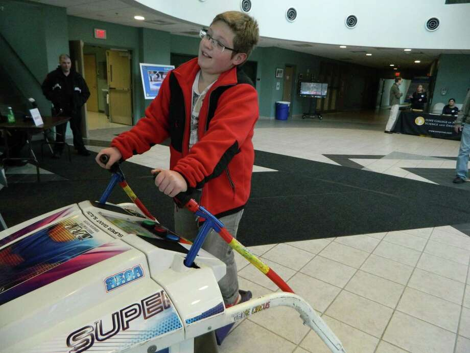 Josh Janack plays an arcade skiing game during the NanOlympics event at the College of Nanoscale Science and Engineering in Albany, N.Y., Saturday, Nov. 9, 2013. NanOlympics offered attendees a look into how nanotechnology will be used in various sports at the 2014 Winter Olympics in Sochi, Russia. The event was part of the college's month-long Nanovember event, which aims to shed light on how nanotechnology is used in various parts of society.