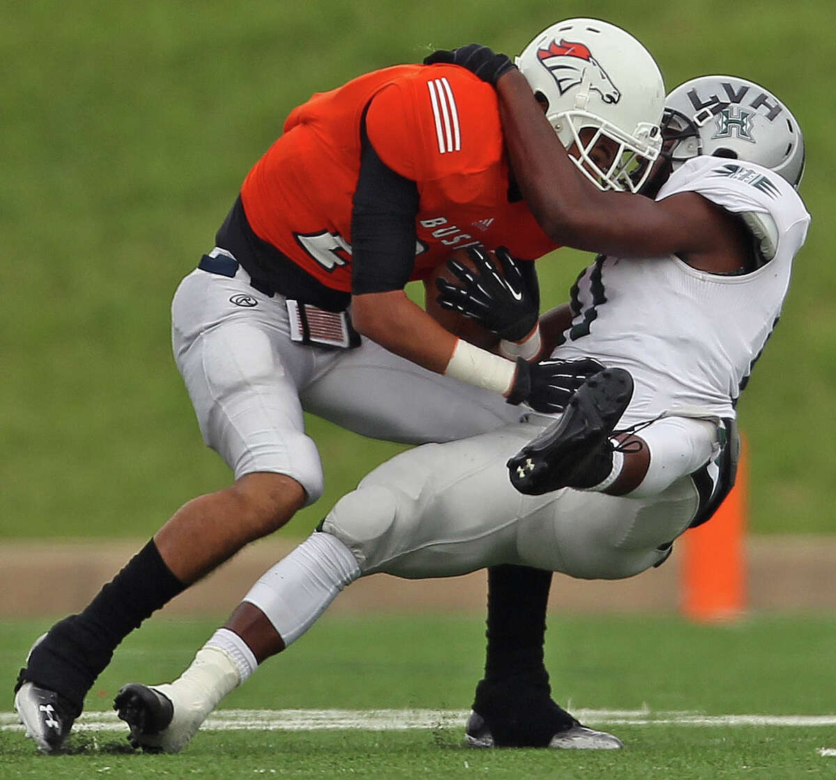 Bush's Donald Monroe, left, is tackled by Hightower's Jowl Williams during the first half of a high school football game, Saturday, November 9, 2013, at Mercer Stadium in Sugar Land.