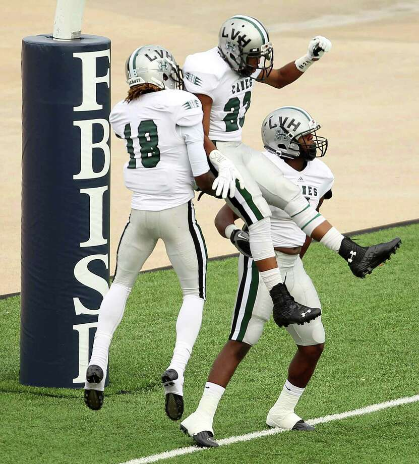 Hightower's Deionte McCann-Smith, left, and Keelan Johnson, center, celebrate Roosevelt Appleton's 45-yard touchdown run during the first half of a high school football game against Bush, Saturday, November 9, 2013, at Mercer Stadium in Sugar Land. Photo: Eric Christian Smith, For The Chronicle
