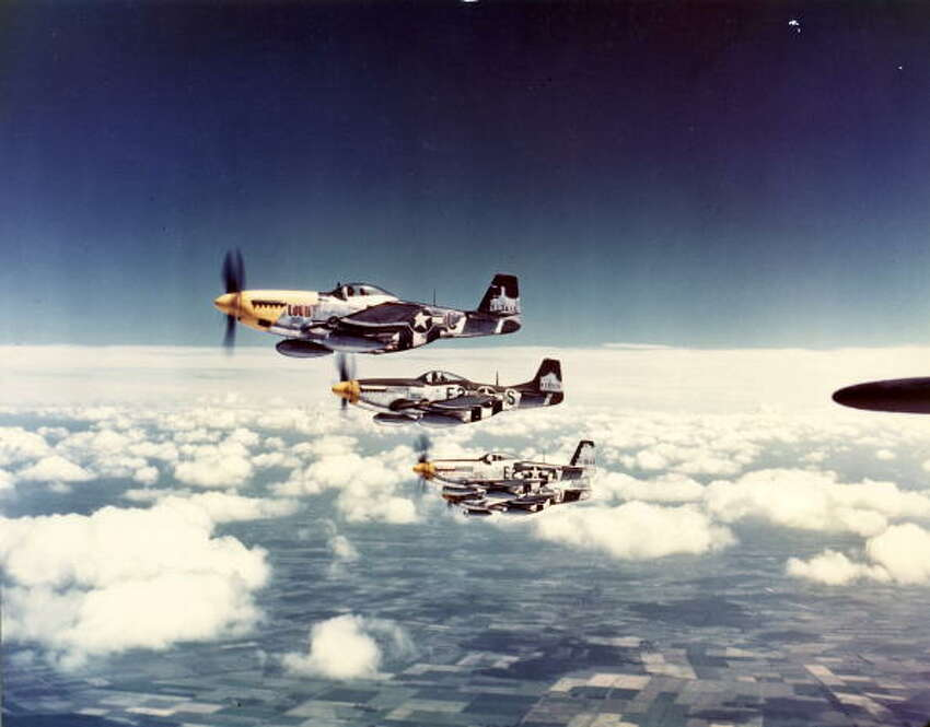Aerial view of a squadron of North American Aviation P-51 Mustang fighter planes (including one nickanemd 'Lou IV') in flight over England, 1940s.