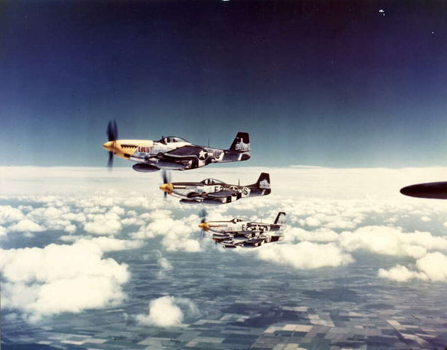 Aerial view of a squadron of North American Aviation P-51 Mustang fighter planes (including one nickanemd 'Lou IV') in flight over England, 1940s. Photo: PhotoQuest, Getty Images / Archive Photos