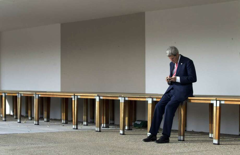 U.S. Secretary of State John Kerry consults his mobile phone prior to a meeting with Iranian Foreign Minister and EU's High Representative for Foreign Affairs, on November 9, 2013, on the third day of talks on Iran's nuclear programme at the Intercontinental Hotel in Geneva Switzerland. Crunch talks between Iran and world powers stretched into an unscheduled third day on November 9 as top diplomats pushed for a deal to end the decade-old standoff over Iran's nuclear programme. AFP PHOTO / POOL / Jason ReedJASON REED/AFP/Getty Images Photo: JASON REED / AFP