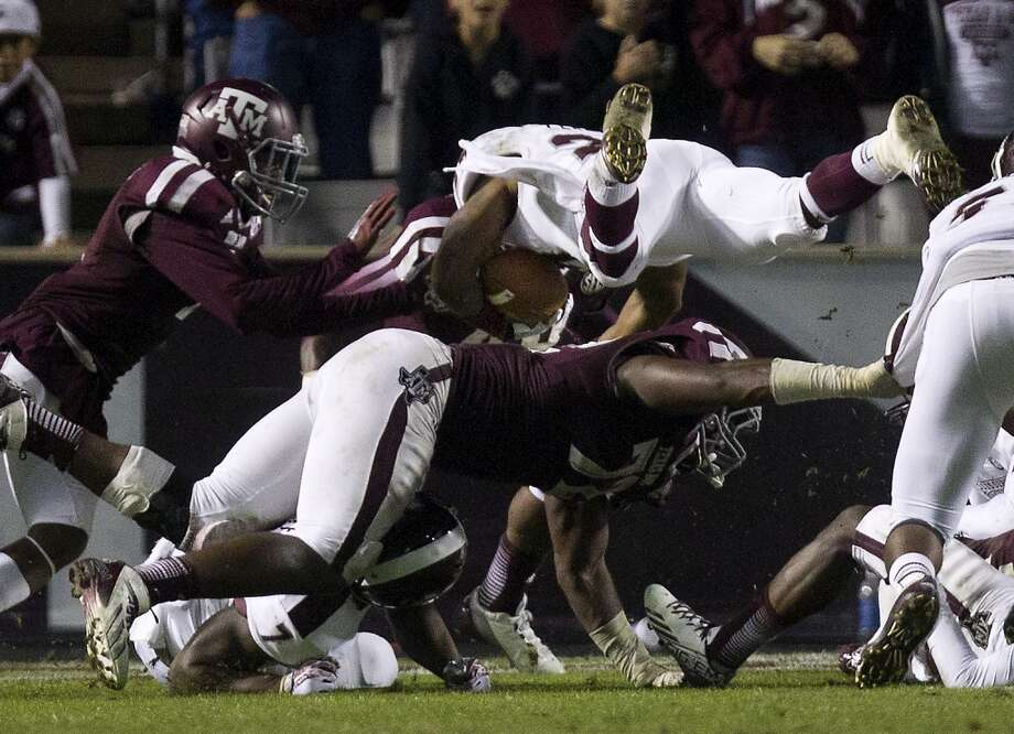 Bulldogs running back LaDarius Perkins leaps over a host of Aggies defenders. Photo: Cody Duty, Houston Chronicle
