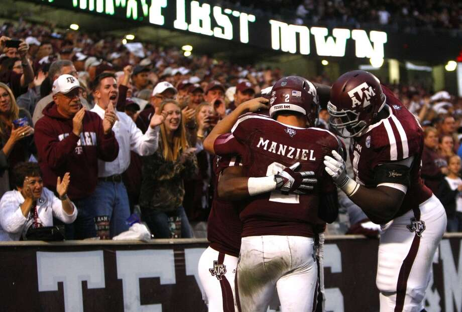 A&M quarterback Johnny Manziel celebrates with teammates after throwing a touchdown pass to running back Trey Williams. Photo: Cody Duty, Houston Chronicle
