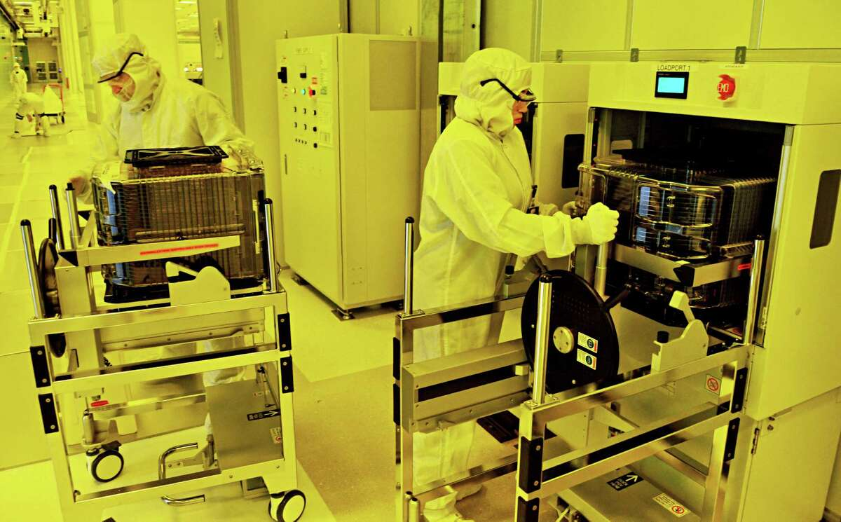 Technicians move containers of G450C wafers into a wafer stocker, at right, before sending them by overhead vehicles back to Nano Fab North from Albany NanoTech's new NanoFab Xtension facility Wednesday Nov. 6, 2013, in Albany, NY. (John Carl D'Annibale / Times Union)