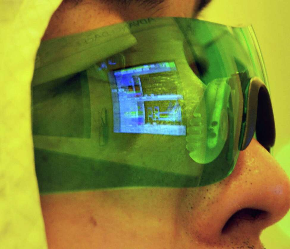 Japanese engineer Kosigi Tetsua's safety glasses reflect a computer readout as he works with the team installing a G450C oxidating furnace in Albany NanoTech's new NanoFab Xtension facility Wednesday Nov. 6, 2013, in Albany, NY. (John Carl D'Annibale / Times Union)