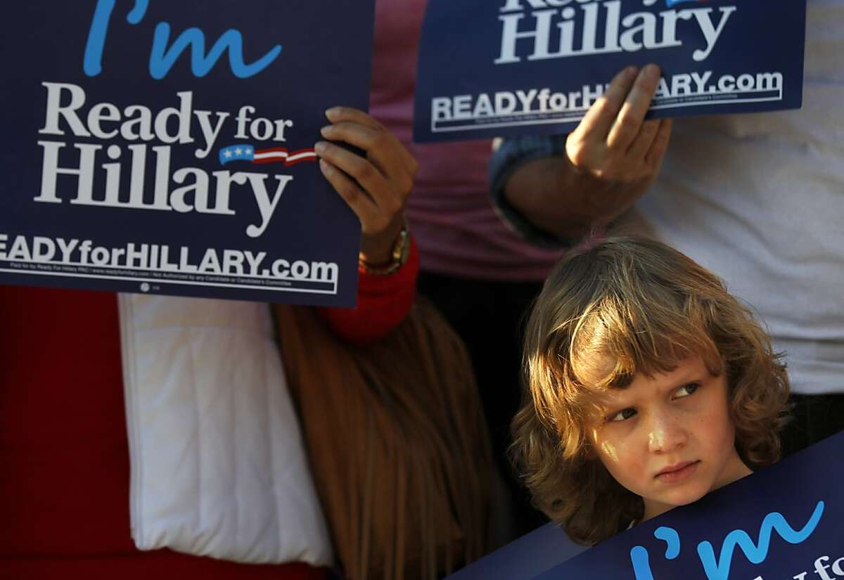Cassidy Drutz, 6, checks out the scene while holding a sign in front of her mother (not visible) Kim Drutz, during a small rally endorsing Hillary Clinton to run for President in the 2016 November 9, 2013 outside of the Moscone Center where Clinton was scheduled to give the keynote speech to the Realtors Conference and Expo in downtown San Francisco, Calif.