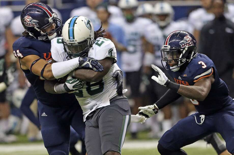 Tulane running back Rob Kelley chugs along with Roadrunner defenders Codie Brooks (94) and Cody Berry trying to stop him as UTSA  hosts Tulane at the Alamodome on November 10, 2013.