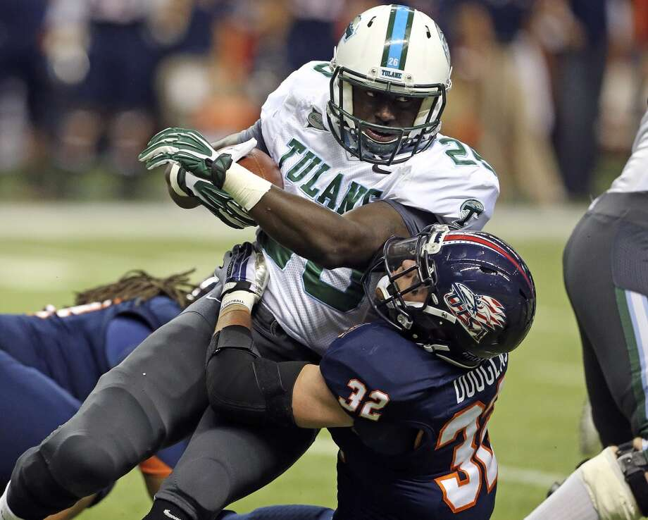Tulane's Orleans Darkwa runs over Drew Douglas as UTSA  hosts Tulane at the Alamodome on November 10, 2013.