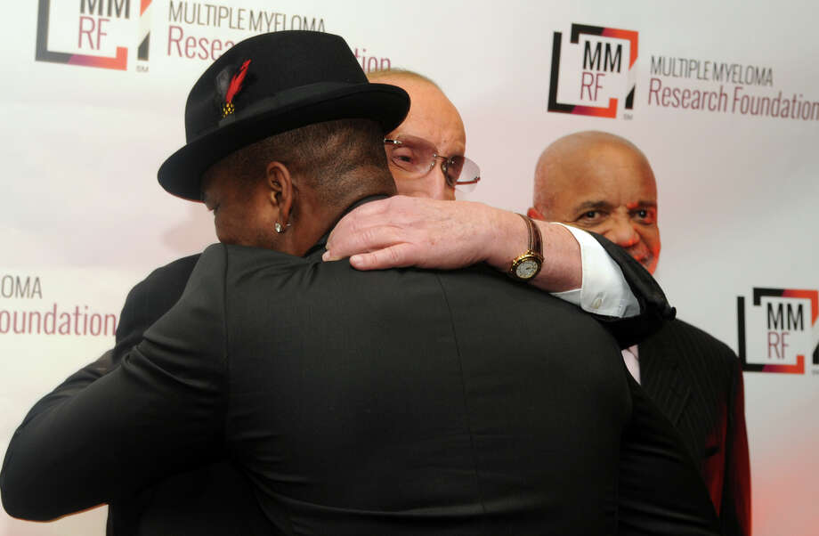 Grammy winning artist Ne-Yo gets a hug from music industry legend Clive Davis as Motown recording legend Berry Gordy looks on at the start of the Multiple Myeloma Research Foundation's 17th Annual Fall Gala. The event recognized Motown Founder Berry Gordy and featured a performance by Grammy winning artist Ne-Yo at the Greenwich Hyatt in Greenwich, Conn., Nov. 9, 2013. The event raised more than $2 million dollars for research. Photo: Keelin Daly / Stamford Advocate Freelance