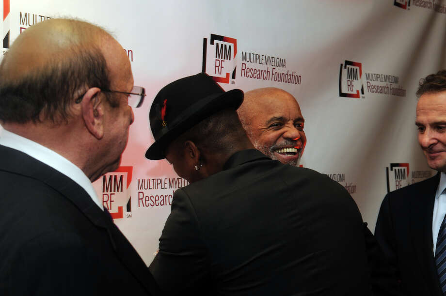 Grammy winning artist Ne-Yo gets a hug from Motown recording legend Berry Gordy as music industry legend Clive Davis looks on at the start of the Multiple Myeloma Research Foundation's 17th Annual Fall Gala. The event recognized Motown Founder Berry Gordy and featured a performance by Grammy winning artist Ne-Yo at the Greenwich Hyatt in Greenwich, Conn., Nov. 9, 2013. The event raised more than $2 million dollars for research. Photo: Keelin Daly / Stamford Advocate Freelance