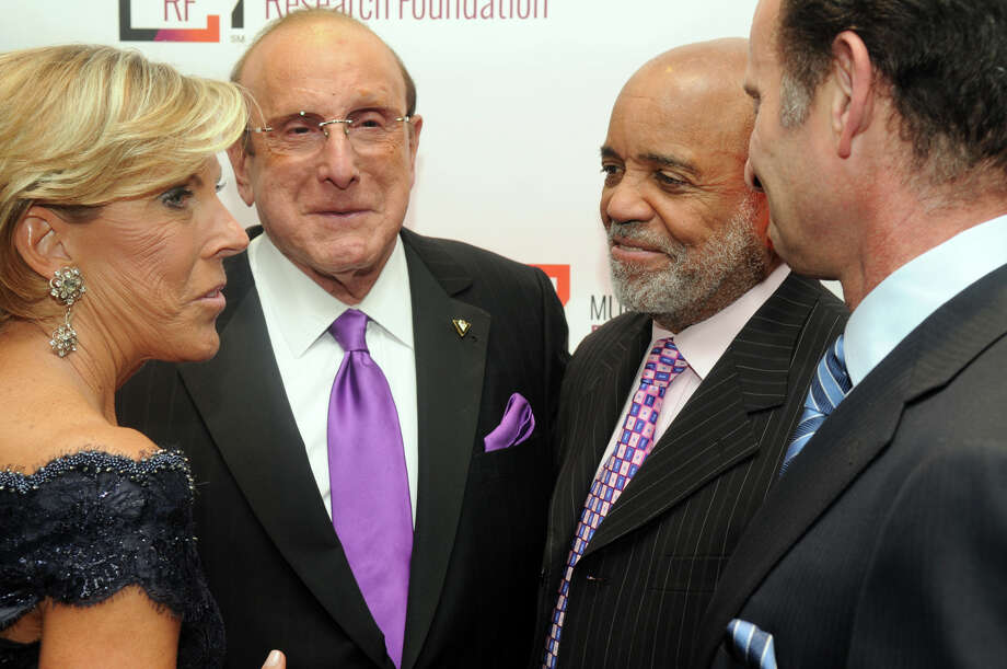 Music industry heavyweights Clive Davis and Berry Gordy chat with Kathy Giusti, founder and CEO of MMRF, and Charles Goldstuck, president and CEO of TouchTunes, at the start of the Multiple Myeloma Research Foundation's 17th Annual Fall Gala. The event recognized Motown Founder Berry Gordy and featured a performance by Grammy winning artist Ne-Yo at the Greenwich Hyatt in Greenwich, Conn., Nov. 9, 2013. The event raised more than $2 million dollars for research. Photo: Keelin Daly / Stamford Advocate Freelance