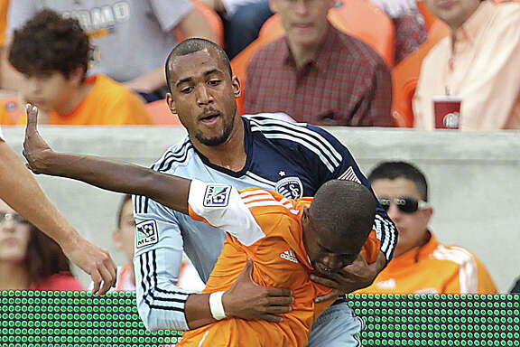 Play becomes a little physical Saturday as Sporting Kansas City  forward Teal Bunbury impedes Dynamo midfielder Boniek Garcia during the first half of the MLS Eastern Conference final match at BBVA Compass Stadium. But no cards were shown to either team.