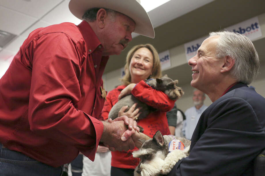Texas Attorney General Greg Abbott holds Bailey while his wife, Cecilia Abbott holds Hershey Bar, two dogs owned by supporter Wayne Musgrove, left, of Mountain Home, as Abbott greets supporters after officially filing paperwork for his candidacy for governor of Texas at the Texas Republican Party headquarters in Austin on Saturday, November 9, 2013. The dogs wore Abbott for Governor buttons and rode in a stroller. Photo: Lisa Krantz, San Antonio Express-News / San Antonio Express-News
