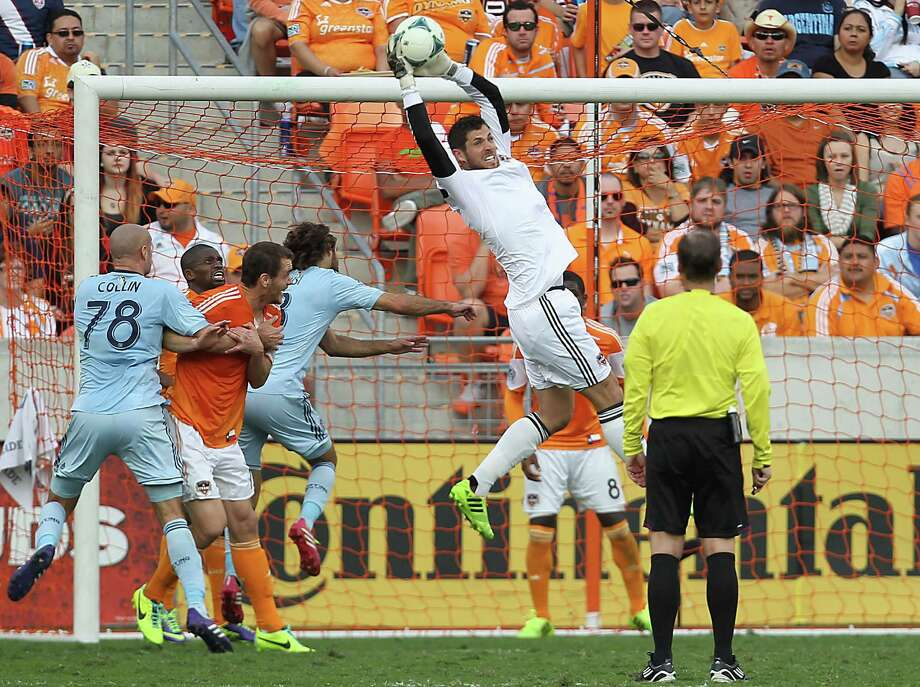 Dynamo keeper Tally Hall pulls down a cross to avert a scoring chance for Sporting Kansas City during Saturday's Eastern Confernce final match. Hall made two saves for his fifth career playoff shutout. Photo: James Nielsen, Staff / © 2013  Houston Chronicle