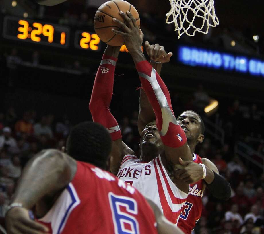 Rockets center Dwight Howard wrestles for control of the ball with Clippers point guard Chris Paul as DeAndre Jordan looks on. Photo: James Nielsen, Houston Chronicle