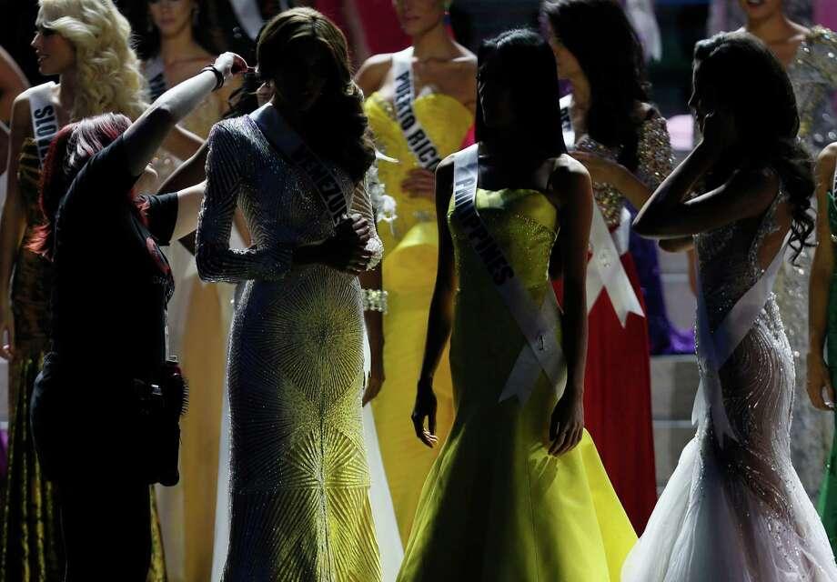 A hair stylist adjusts a Miss Venezuela Gabriela Isler's hair during the 2013 Miss Universe pageant in Moscow, Russia, on Saturday, Nov. 9, 2013. Gabriela Isler won the Miss Universe 2013 title. Photo: Pavel Golovkin, AP / AP2013