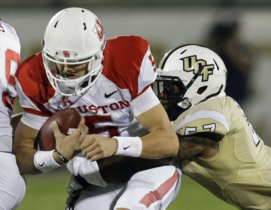 Nov. 9: USF 19, UH 14Record: 7-2  Houston quarterback John O'Korn, left, is thrown for a loss as he is tackled by Central Florida's Troy Gray during the first half of an NCAA college football game in Orlando, Fla., Saturday, Nov. 9, 2013. (AP Photo/John Raoux) Photo: John Raoux, Associated Press
