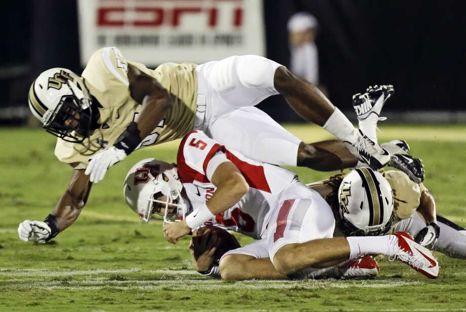 Houston quarterback John O'Korn (5) is tackled by Central Florida linebacker Troy Gray, top, and defensive back Jordan Ozerities, right, during the first half of an NCAA college football game in Orlando, Fla., Saturday, Nov. 9, 2013. (AP Photo/John Raoux) Photo: John Raoux, Associated Press