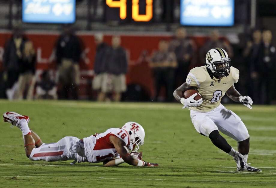 Central Florida running back Storm Johnson (8) gains yardage as he gets past Houston's Adrian McDonald (16) during the first half of an NCAA college football game in Orlando, Fla., Saturday, Nov. 9, 2013. (AP Photo/John Raoux) Photo: John Raoux, Associated Press