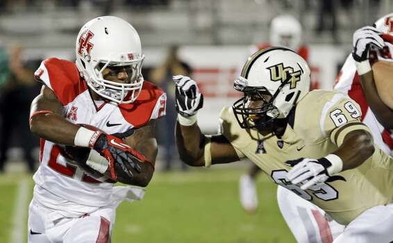 Houston running back Ryan Jackson, left, looks for a way around Central Florida's Thomas Niles (69) during the first half of an NCAA college football game in Orlando, Fla., Saturday, Nov. 9, 2013. (AP Photo/John Raoux) Photo: John Raoux, Associated Press