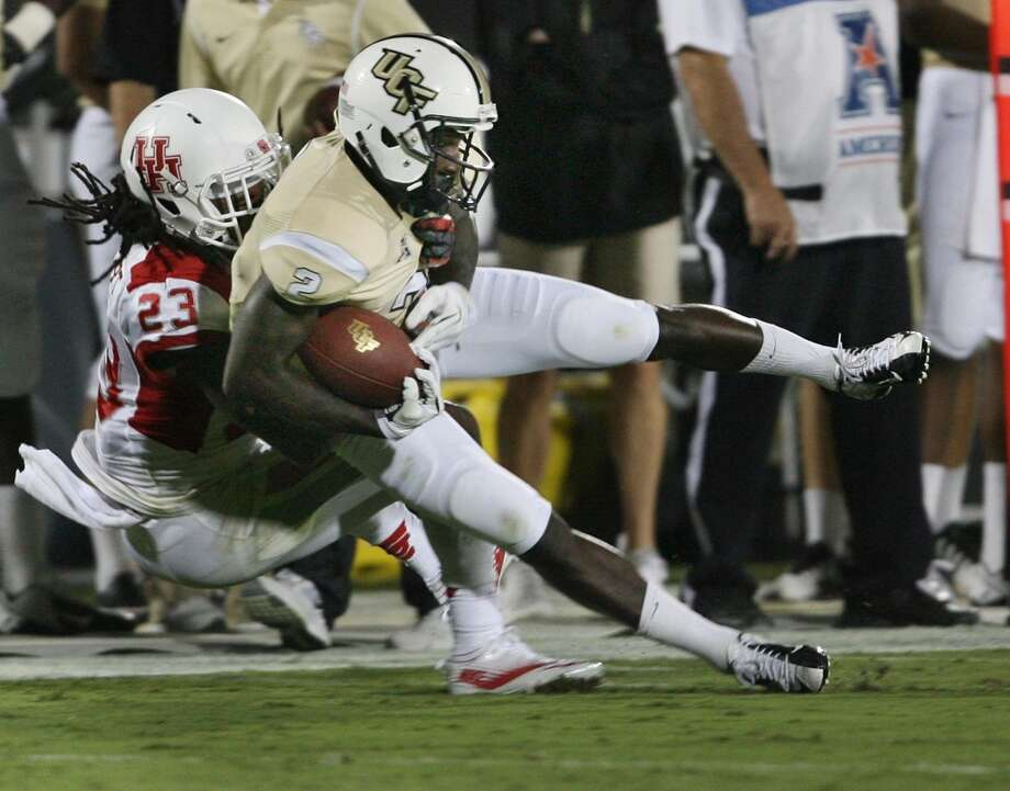 Wide receiver Jeff Godfrey (2) of Central Florida comes down with a reception as defensive back Trevon Stewart (23) of Houston drags him down in the first half at Bright House Networks Stadium in Orlando, Fla., on Saturday, Nov. 9, 2013. (Stephen M. Dowell/Orlando Sentinel/MCT) Photo: Stephen M. Dowell, McClatchy-Tribune News Service