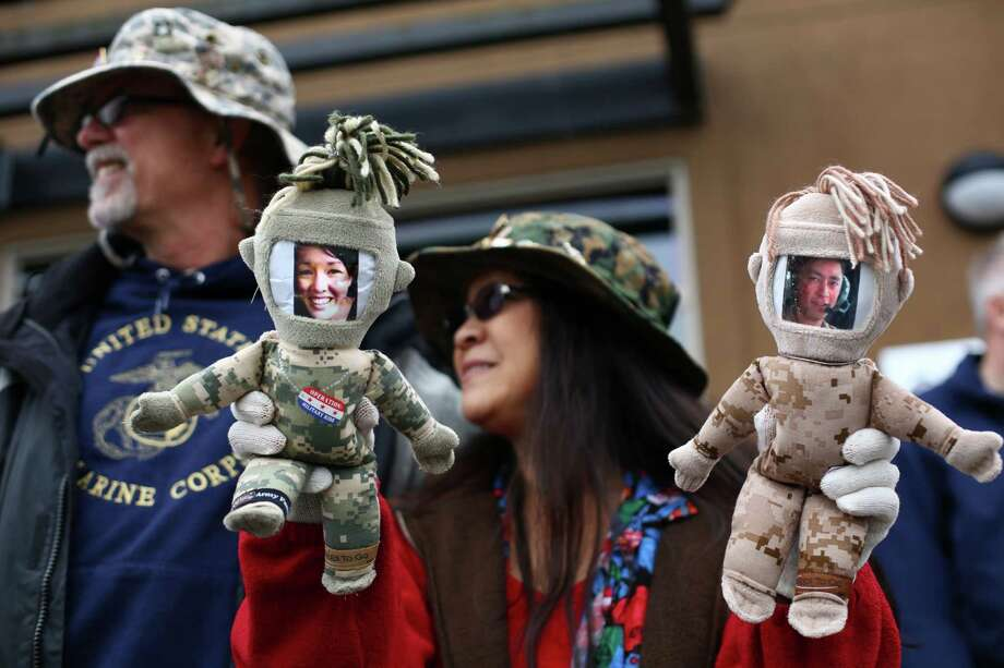 "Jimi Paulson holds ""deployment dolls"" affixed with photographs of her deployed daughter and son, Army Sgt. Keri Herrera, left, and Marine Sgt. Erik Paulson, as she watches the 48th annual Auburn Veterans Day Parade with her husband Kurt Paulson. Photo: JOSHUA TRUJILLO, SEATTLEPI.COM / SEATTLEPI.COM"
