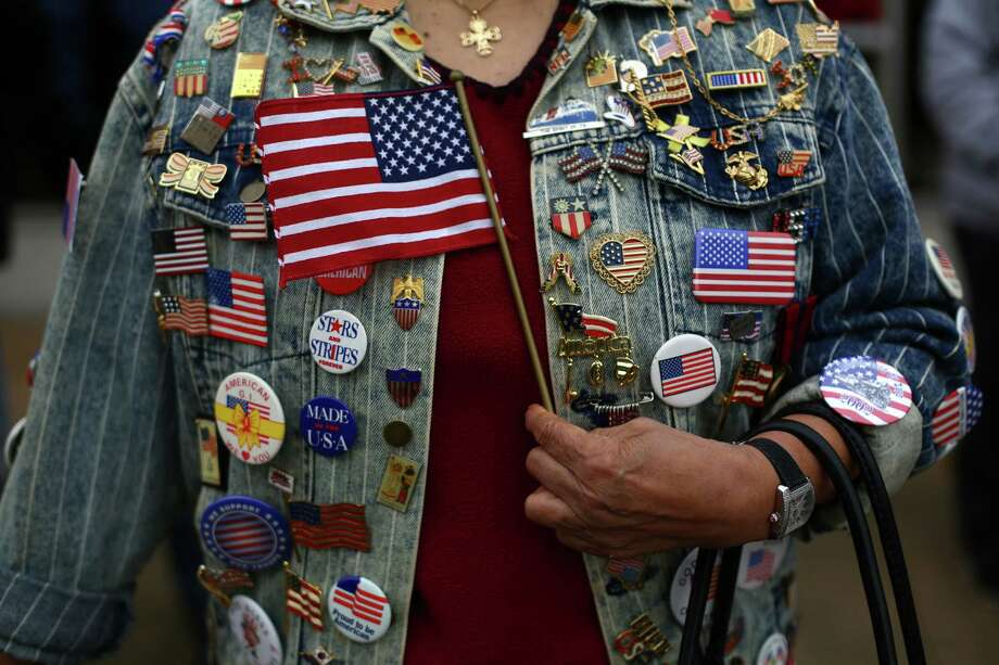 A woman holds a flag against her pin-decorated jacket during the 48th annual Auburn Veterans Day Parade. Photo: JOSHUA TRUJILLO, SEATTLEPI.COM / SEATTLEPI.COM
