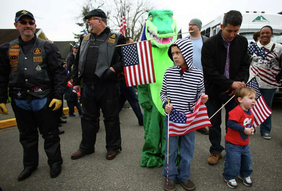 Gator, the Green River Community College mascot, holds a flag with his mouth during the 48th annual Auburn Veterans Day Parade. Photo: JOSHUA TRUJILLO, SEATTLEPI.COM / SEATTLEPI.COM