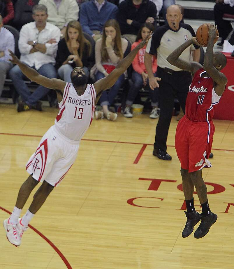 Clippers shooting guard Jamal Crawford right, shoots the ball over Rockets shooting guard James Harden. Photo: James Nielsen, Houston Chronicle