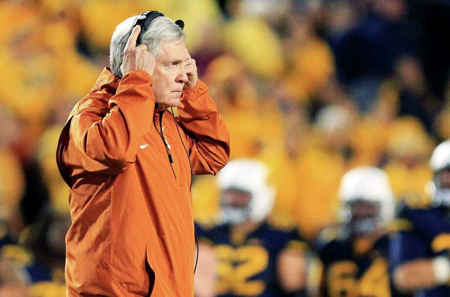 Texas coach Mack Brown walks across the field after an injury to one of his players in the second quarter of an NCAA college football game against West Virginia in Morgantown, W.Va., on Saturday, Nov. 9, 2013. Texas won 47-40 in overtime. (AP Photo/Christopher Jackson) Photo: Chris Jackson, Associated Press / FR170573