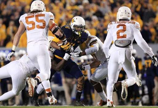 West Virginia's Kevin White (11) is brought down by several Texas defenders during the second quarter of an NCAA college football game in Morgantown, W.Va., on Saturday, Nov. 9, 2013. (AP Photo/Christopher Jackson) Photo: Chris Jackson, Associated Press
