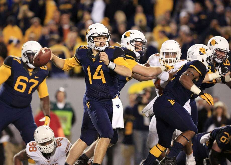 West Virginia quarterback Paul Millard (14) throws to a receiver during the second quarter of an NCAA college football game against Texas in Morgantown, W.Va., on Saturday, Nov. 9, 2013. (AP Photo/Christopher Jackson) Photo: Chris Jackson, Associated Press