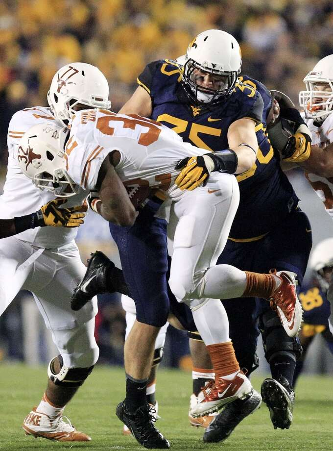 West Virginia's Nick Kwiatkoski (35) tackles Texas's Johnathan Gray (32) during the second quarter of an NCAA college football game in Morgantown, W.Va., on Saturday, Nov. 9, 2013. Texas won 47-40 in overtime. (AP Photo/Christopher Jackson) Photo: Chris Jackson, Associated Press