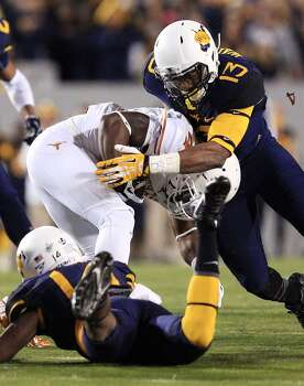 West Virginia's Sean Walters (13) and Ricky Rumph, bottom, tackle Texas's Daje Johnson during the first quarter of an NCAA college football game in Morgantown, W.Va., on Saturday, Nov. 9, 2013. (AP Photo/Christopher Jackson) Photo: Chris Jackson, Associated Press