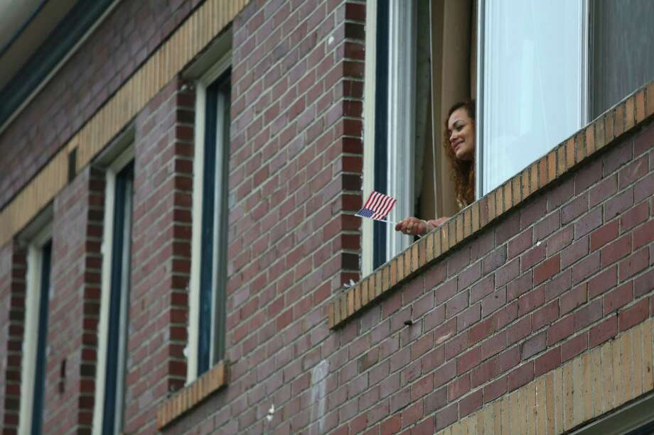 A woman watches from a window above during the 48th annual Auburn Veterans Day Parade. Photo: JOSHUA TRUJILLO, SEATTLEPI.COM / SEATTLEPI.COM