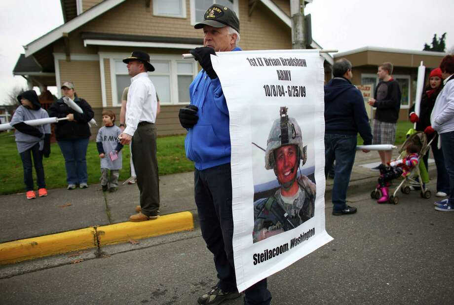 Paul Bradshaw holds of banner featuring the face of his late son 1st Lt. Brian Bradshaw, who was killed in Afghanistan's Paktia province in 2009. Bradshaw marched with the Gold Star Mothers during the 48th annual Auburn Veterans Day Parade. Photo: JOSHUA TRUJILLO, SEATTLEPI.COM / SEATTLEPI.COM