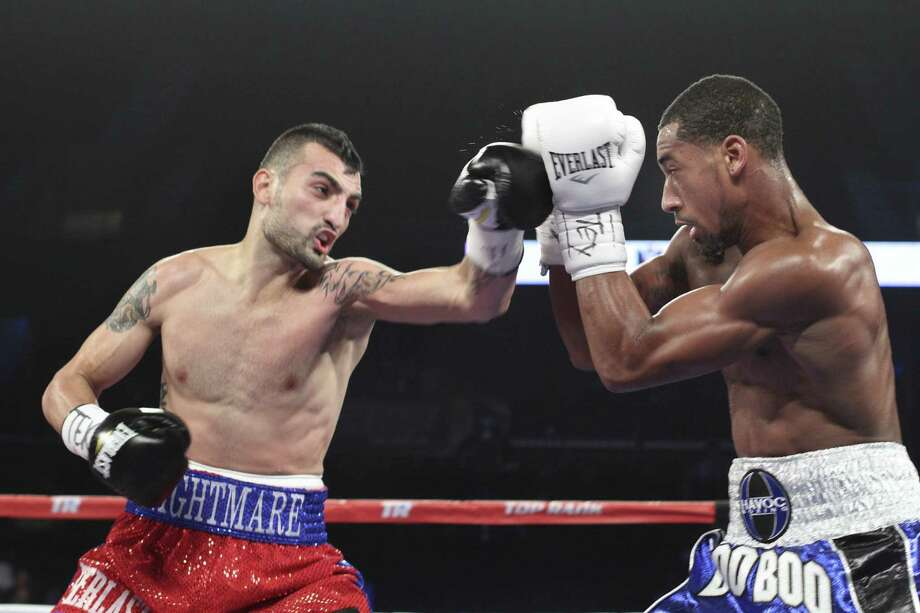 Demetrius Andrade (right), who won a split decision for the WBO super welterweight title, blocks a left from Vanes Martirosyan. Photo: George Tuley / For The Corpus Christi Caller-Times