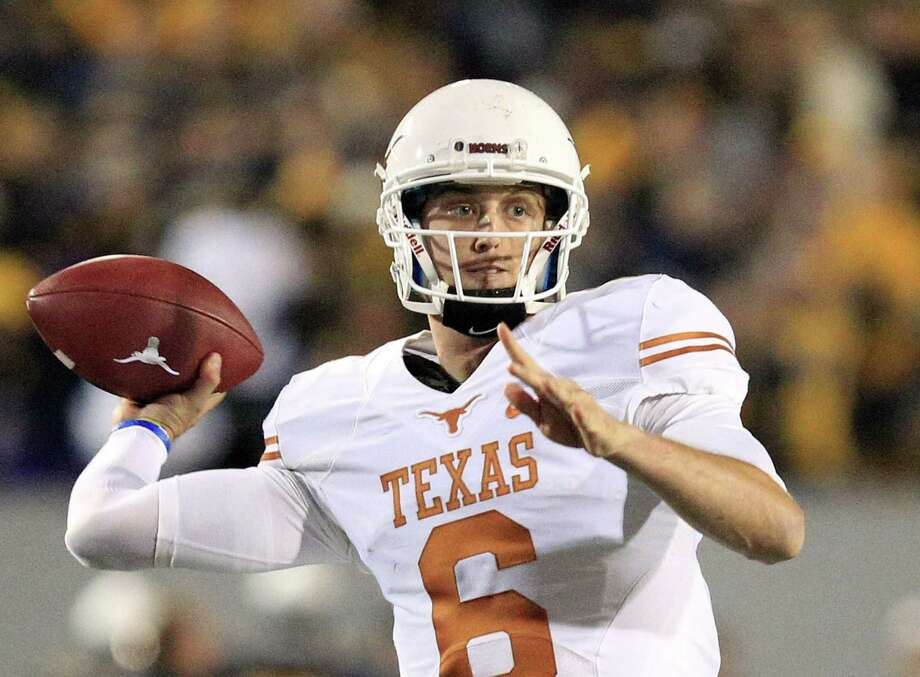 Texas quarterback Case McCoy looks for a receiver late in the fourth quarter of the Longhorns' comeback overtime victory at West Virginia, keeping UT unbeaten in Big 12 play at 6-0. Photo: Chris Jackson / Associated Press