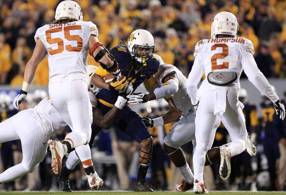 West Virginia's Kevin White (11) is brought down by several Texas defenders during the second quarter of an NCAA college football game in Morgantown, W.Va., on Saturday, Nov. 9, 2013. (AP Photo/Christopher Jackson) Photo: Associated Press