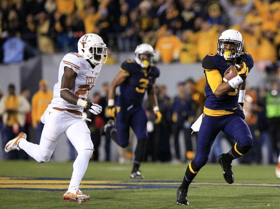 West Virginia's Mario Alford, right, looks over his shoulder as he runs past Texas' Duke Thomas for a touchdown during the fourth quarter of an NCAA college football game in Morgantown, W.Va., on Saturday, Nov. 9, 2013. Texas won 47-40 in overtime. (AP Photo/Christopher Jackson) Photo: Associated Press