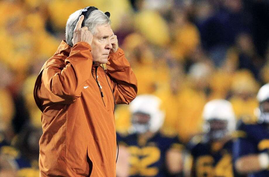 Texas coach Mack Brown walks across the field after an injury to one of his players in the second quarter of an NCAA college football game against West Virginia in Morgantown, W.Va., on Saturday, Nov. 9, 2013. Texas won 47-40 in overtime. (AP Photo/Christopher Jackson) Photo: Associated Press