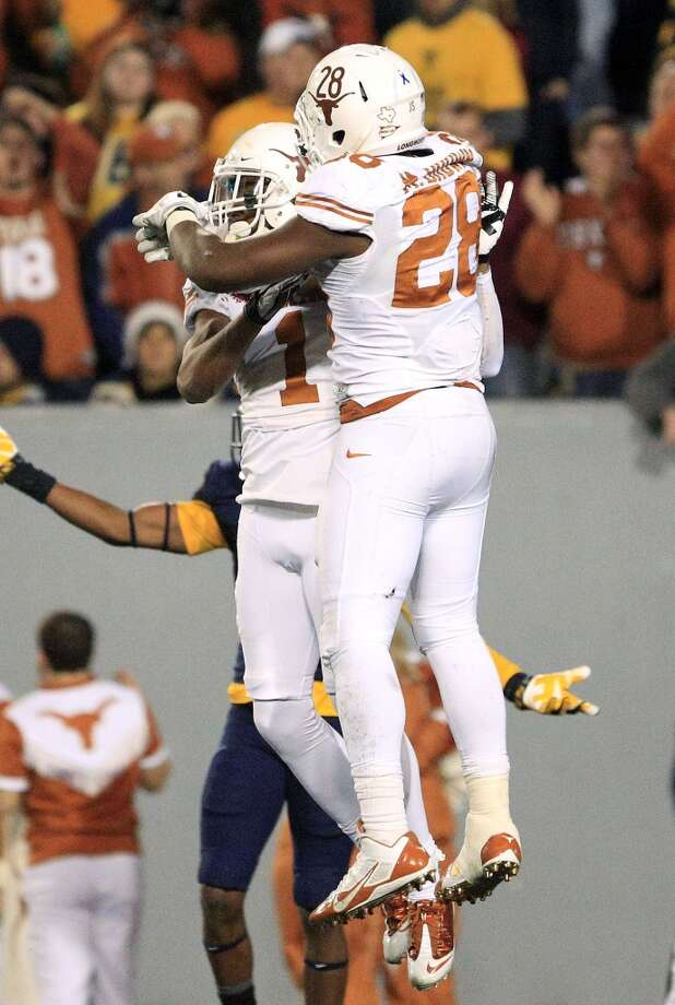 Texas' Mike Davis (1) and Malcolm Brown (28) celebrate Davis' touchdown during the fourth quarter of their NCAA college football game in Morgantown, W.Va., on Saturday, Nov.9, 2013. Texas won 47-40 in overtime. (AP Photo/Christopher Jackson) Photo: Associated Press