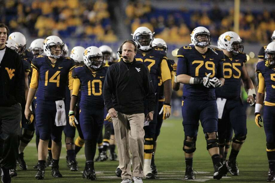 West Virginia coach Dana Holgorsen walks with some of his players during a timeout in the fourth quarter of their NCAA college football game against Texas in Morgantown, W.Va., on Saturday, Nov.9, 2013. Texas won 47-40 in overtime. (AP Photo/Christopher Jackson) Photo: Associated Press