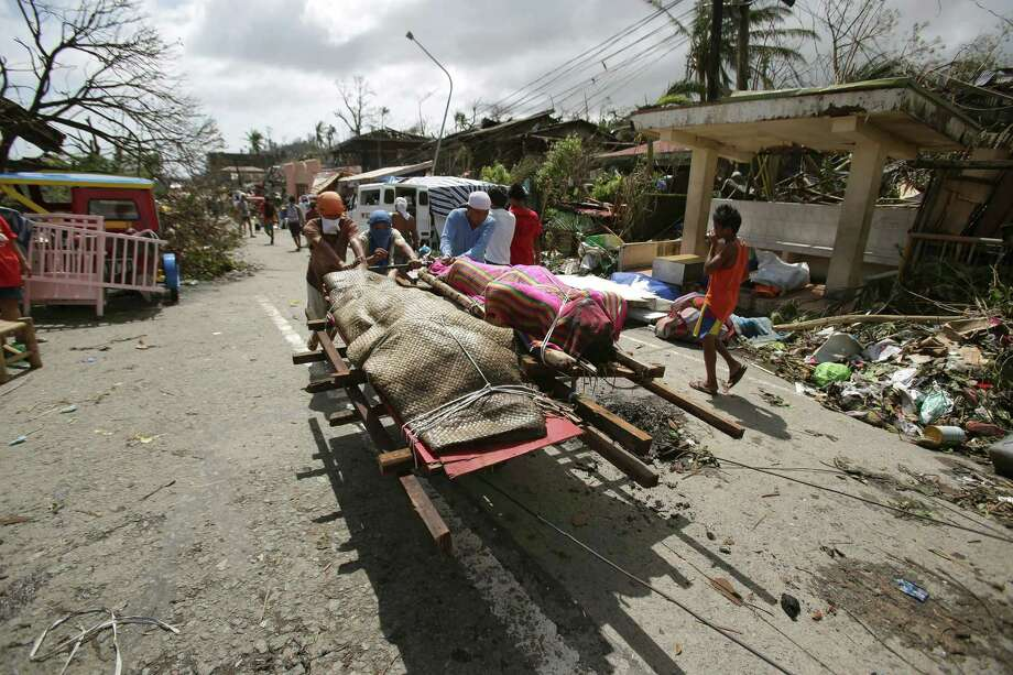 Residents push dead bodies on a cart after strong waves caused by Typhoon Haiyan slammed into Tacloban city, Leyte province central Philippines on Sunday, Nov. 10, 2013. Typhoon Haiyan, one of the strongest storms on record, slammed into six central Philippine islands on Friday leaving a wide swath of destruction and hundreds of people dead. Photo: Aaron Favila, AP / AP