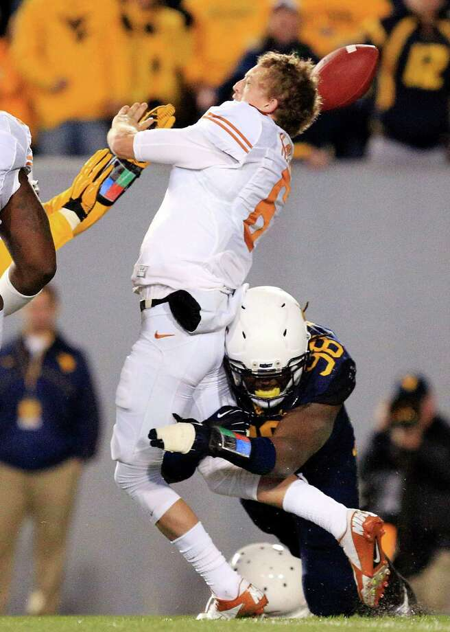 Texas' Case McCoy stands tall despite losing his helmet while being sacked by West Virginia's Will Clarke during the second quarter Saturday night. Photo: Chris Jackson, FRE / FR170573