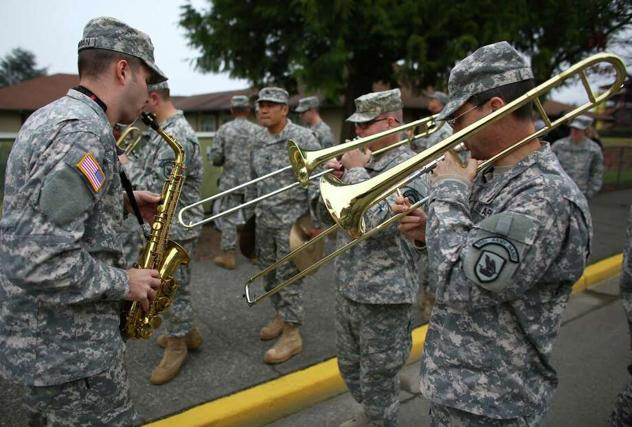 From left, Sgt. Matt Wenman, Sgt. Dan Ruiter and Sgt. Dan Ray warm up with the National Guard band before the 48th annual Auburn Veterans Day Parade. Photo: JOSHUA TRUJILLO, SEATTLEPI.COM / SEATTLEPI.COM