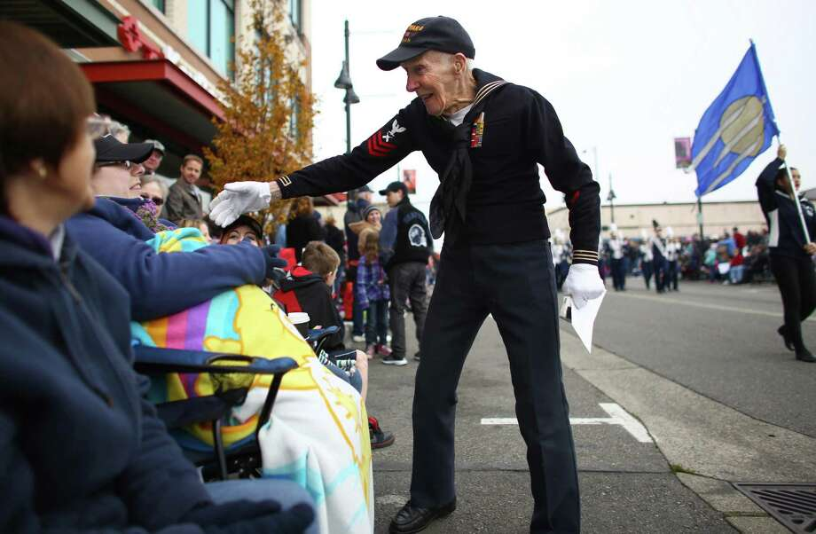 U.S. Navy World War II veteran Donald Hanson, 91, shakes hands with spectators as he marches along the route. Hanson was one of the featured honorees at the parade. Photo: JOSHUA TRUJILLO, SEATTLEPI.COM / SEATTLEPI.COM